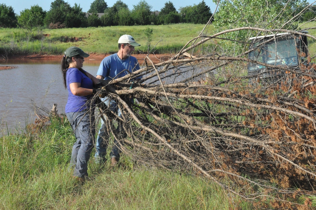 """Tinker Natural Resource Manager John Krupovage and Donna Nowlan, spend a hot July morning removing fallen cedar trees on Tinker Air Force Base, and dragging them into Primrose Pond near base housing and the Child Development Center. Cedar trees are an invasive species in Oklahoma and once moved into the pond, which lacks covered structure on the shore line, they provide habitat for the forage fish and bass who reside in the water. Kuprovage said that providing this quality habitat also leads to """"trophy bass."""" (U.S. Air Force photo/Megan Prather)"""