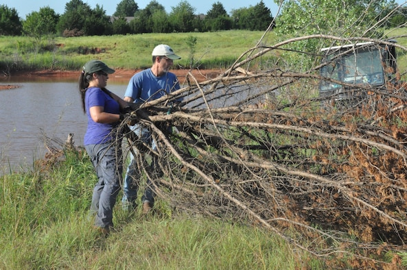 "Tinker Natural Resource Manager John Krupovage and Donna Nowlan, spend a hot July morning removing fallen cedar trees on Tinker Air Force Base, and dragging them into Primrose Pond near base housing and the Child Development Center. Cedar trees are an invasive species in Oklahoma and once moved into the pond, which lacks covered structure on the shore line, they provide habitat for the forage fish and bass who reside in the water. Kuprovage said that providing this quality habitat also leads to ""trophy bass."" (U.S. Air Force photo/Megan Prather)"