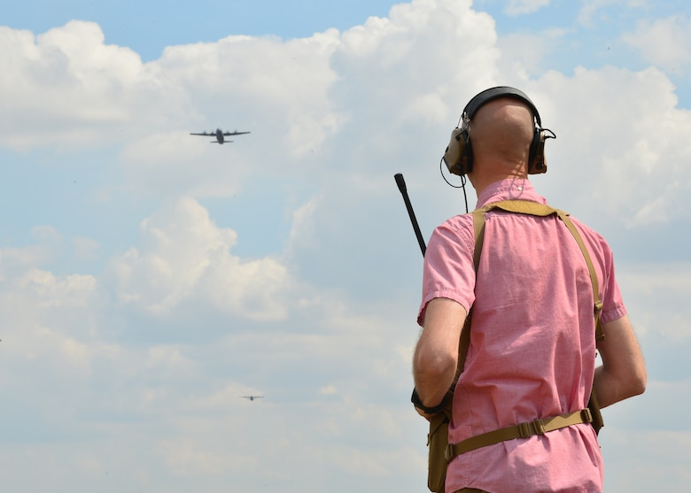 U.S. Air Force Capt. Jacob Kopp, 435th Contingency Response Squadron landing zone safety officer, watches U.S. Air Force C-130J Super Hercules flying over a landing zone at Powidz Air Base, Poland. During Aviation Rotation 19-3, a bilateral exercise between U.S. and Poland, landing and drop zones were prepared by members of the 435th CRS to allow pilots a diverse training opportunity. (U.S. Air Force photo by Staff Sgt. Jimmie D. Pike)