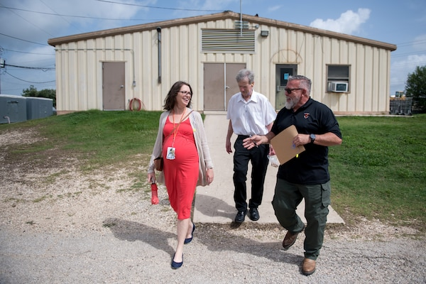 Melissa Little, 59th Medical Wing behavioral health preventive medicine researcher (left), professor Robert Klesges, and Jerry Britt, 341st Training Squadron adoptions and dispositions coordinator, tour the military working dogs (MWDs) kennel June 26, 2019, at Joint Base San Antonio, Texas.