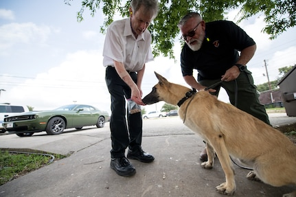 Professor Robert Klesges provides a treat to a military working dog as Jerry Britt, 341st Training Squadron adoptions and dispositions coordinator, monitors its behavior June 26, 2019, at Joint Base San Antonio, Texas.
