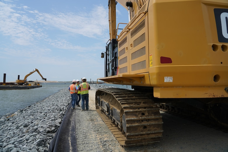 U.S. Army Corps of Engineers, Baltimore District employees Sean Fritzges, a construction representative, and Katie Perkins, a civil engineer, discuss Poplar Island expansion construction progress with a contractor on-site of the expansion July 11, 2019.