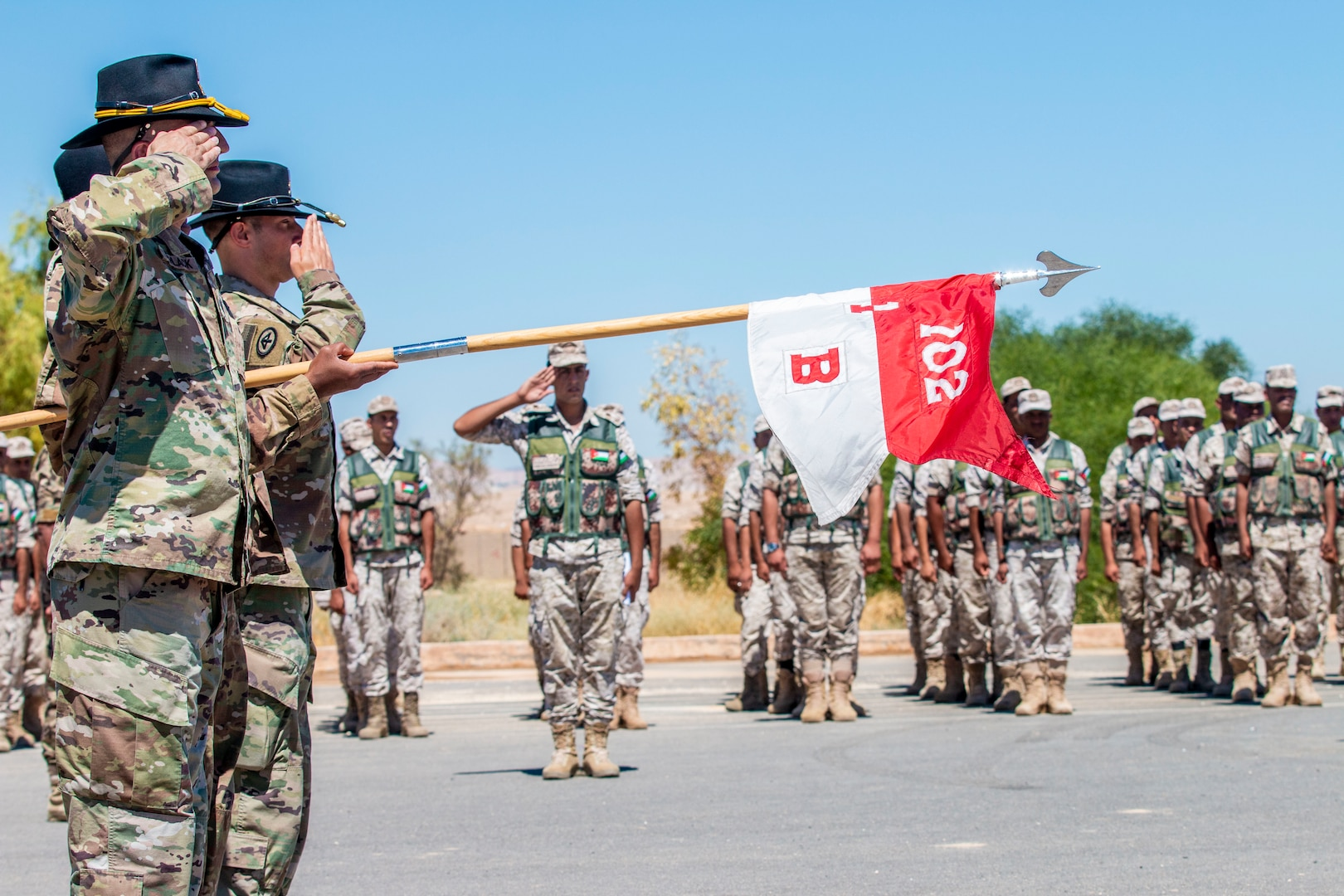 New Jersey National Guard Soldiers, with 1st Squadron, 102nd Calvary Regiment, and Jordan Border Guard Force Soldiers, with the 7th Mechanized Battalion, 48th Mechanized Brigade, render a salute to the Jordanian and American National Anthems during the Jordan Operational Engagement Program (JOEP) opening ceremony July 14, 2019. JOEP is a 14-week individual and collective training, as well as a military partnership between Jordan and America.