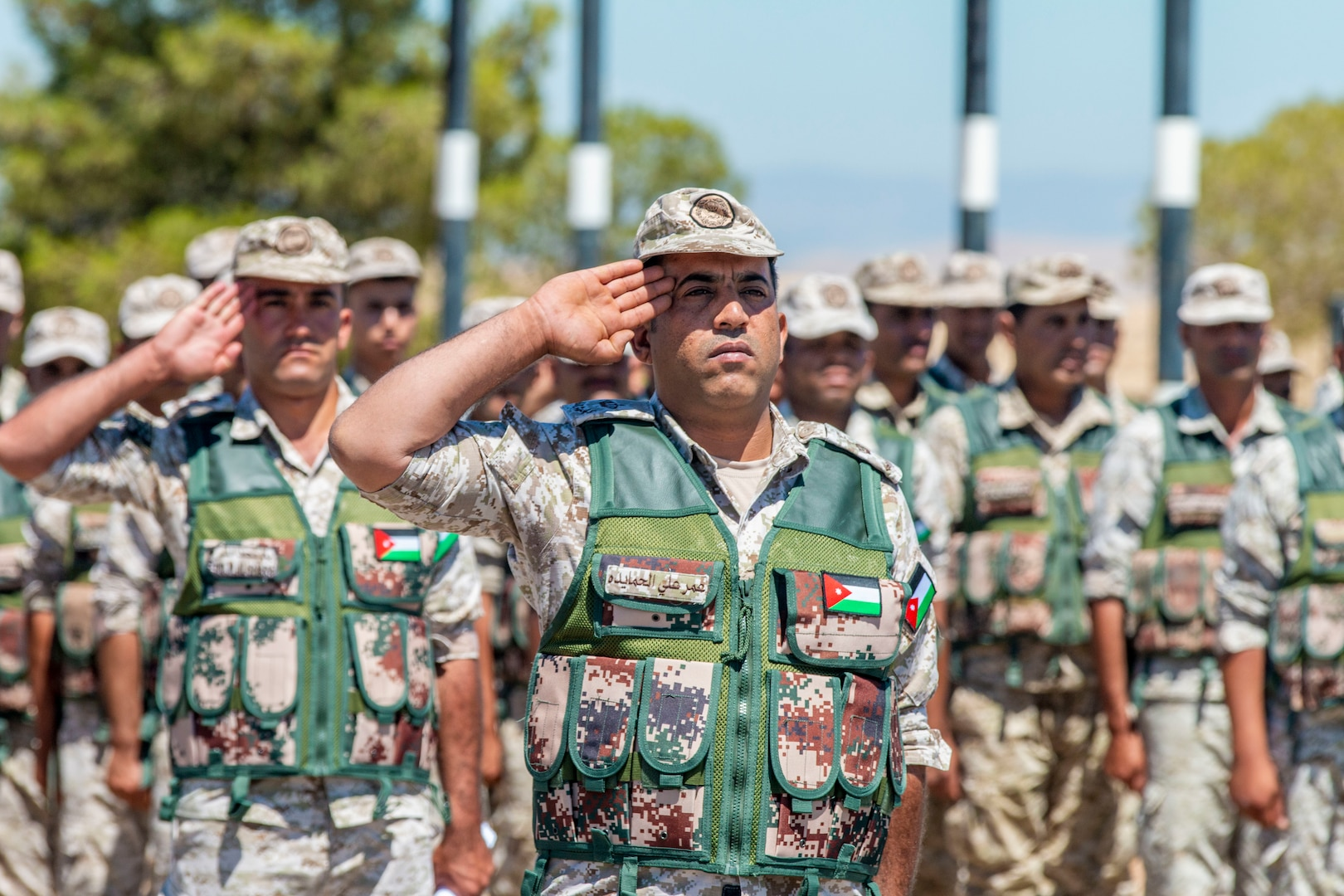 Jordan Border Guard Force Soldiers, with the 7th Mechanized Battalion, 48th Mechanized Brigade, render a salute to the Jordanian and American National Anthems during the Jordan Operational Engagement Program (JOEP) opening ceremony July 14, 2019. JOEP is a 14-week individual and collective training, as well as a military partnership between Jordan and America.