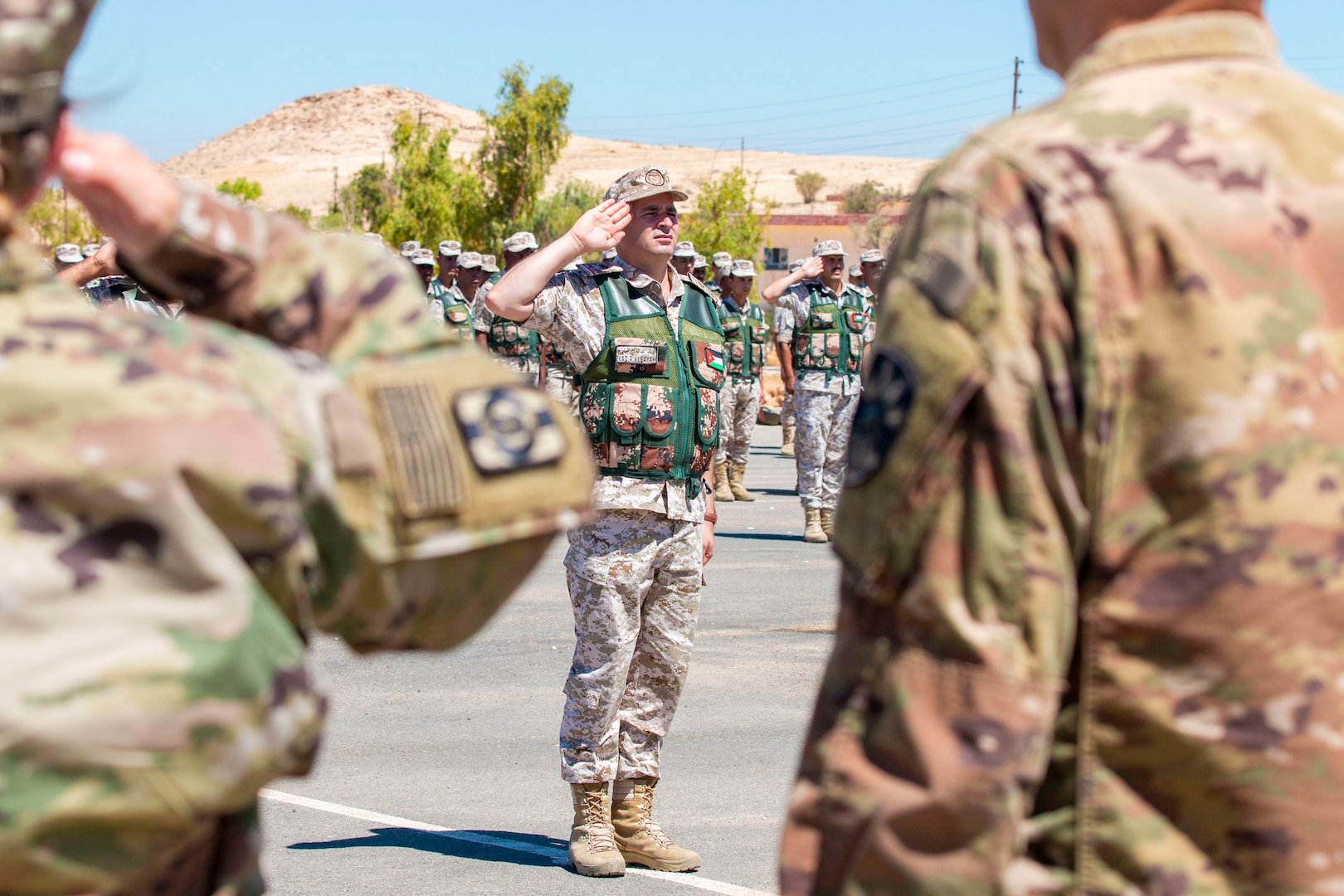 U.S. Army Soldiers and Jordan Border Guard Force Soldiers, with the 7th Mechanized Battalion, 48th Mechanized Brigade, render a salute to the Jordanian and American National Anthems during the Jordan Operational Engagement Program (JOEP) opening ceremony July 14, 2019. JOEP is a 14-week individual and collective training, as well as a military partnership between Jordan and America.