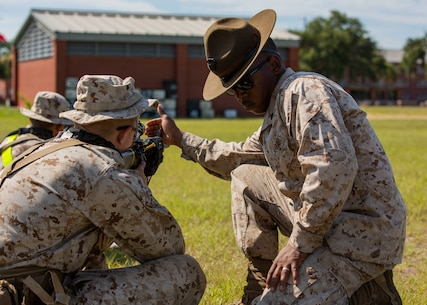 Marksmanship Instructor Sgt. Cedricxavier Hart helps a recruit with  Golf Company, 2nd Recruit Training Battalion, sight in to his Rifle Combat Optic during grass week on Marine Corps Recruit Depot Parris Island, S.C. July 25, 2019. Grass week teaches recruits shooting positions and weapon safety rules for tables 1 and 2. Hart is a native of Nashville, Tennessee. (U.S. Marine Corps photo by Cpl. Isabella Ortega)