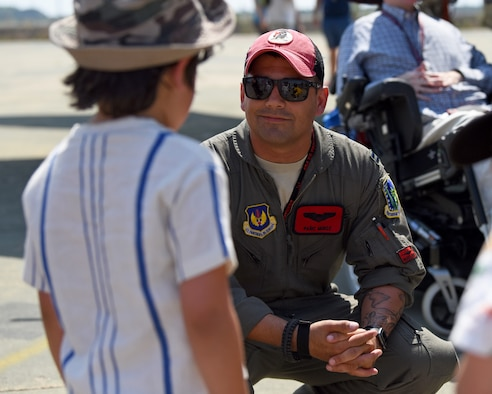 A 494th Fighter Squadron pilot talks to a young boy during Royal Air Force Marham's annual Friends and Family Day July 25, 2019. The 48th Fighter Wing also provided two F-15E Strike Eagles and aircrews to engage with the community alongside their RAF counterparts. (U.S. Air Force photo by Airman 1st Class Madeline Herzog)