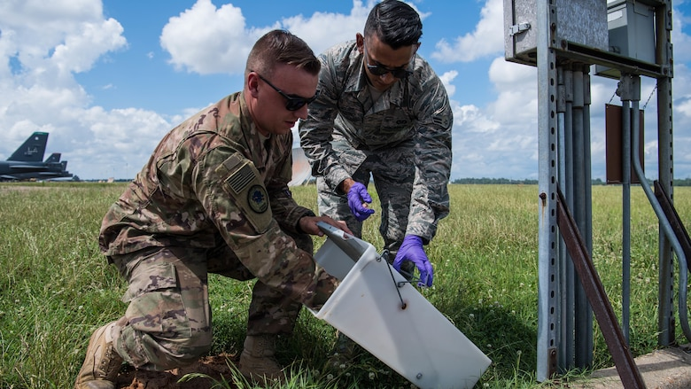 Staff Sgt. Christopher T. Cooper, 2nd Civil Engineer Squadron pest management journeyman, and Airman 1st Class Alberto Montesino (right), a 2nd CES pest management apprentice, set a skunk trap at Barksdale Air Force Base, Louisiana, June 6, 2019. Dealing with pests ranging from mosquitoes to wild dogs, the 2nd CES Ppest Mmanagement shop works to ensure no disease, injury or obstruction can hinder the safety of the mission, Airmen and their families. (U.S. Air Force photo by Airman Jacob B. Wrightsman)