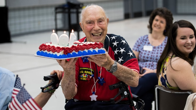 Retired Col. Steven L. dePyssler, 2nd Missions Support Group retiree affairs director, holds his birthday cake during his 100th birthday celebration at the Bossier City Civic Center, Bossier City, Louisiana, July 19, 2019. dePysssler was born July 21, 1919 in Chicago, Illinois. (U.S. Air Force photo by Airman Jacob B. Wrightsman)