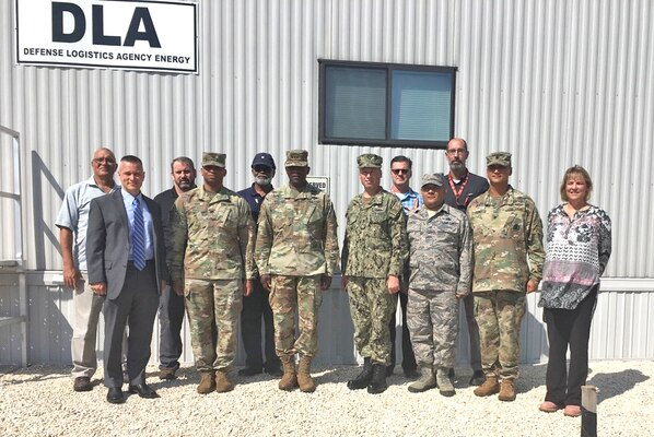 a group of military and civilian personnel pose for a photo