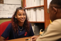 """Staff Sgt. Damali Alliman discusses potential job opportunities in the Marine Corps with a poolee at Recruiting Substation Bridgeport, Bridgeport, Connecticut, July 18, 2019. Alliman recently earned the title """"Centurion"""" by recruiting 100 individuals into the Marine Corps during his time on recruiting duty."""