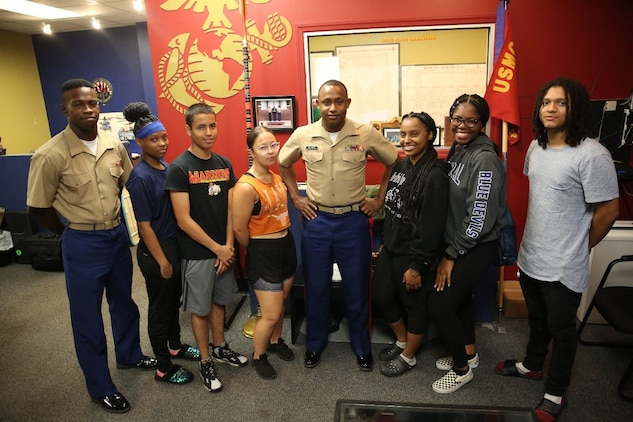 """Staff Sgt. Damali Alliman poses with his group of future Marines at Recruiting Substation Bridgeport, Bridgeport, Connecticut, July 18, 2019. Alliman recently won the """"Centurion"""" for recruiting 100 individuals into the Marine Corps during his 36 month tour on recruiting duty."""