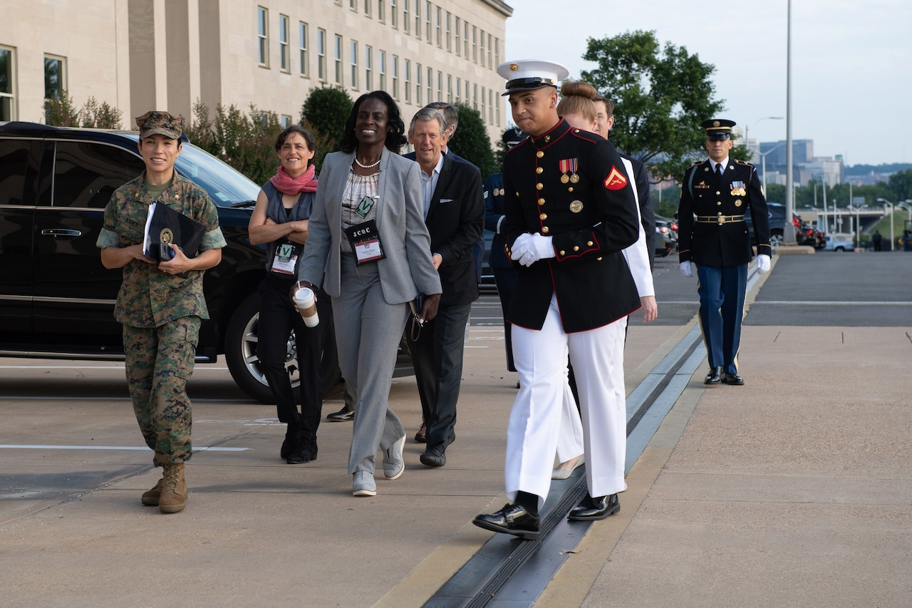 Service members walk with civilians outside the Pentagon.