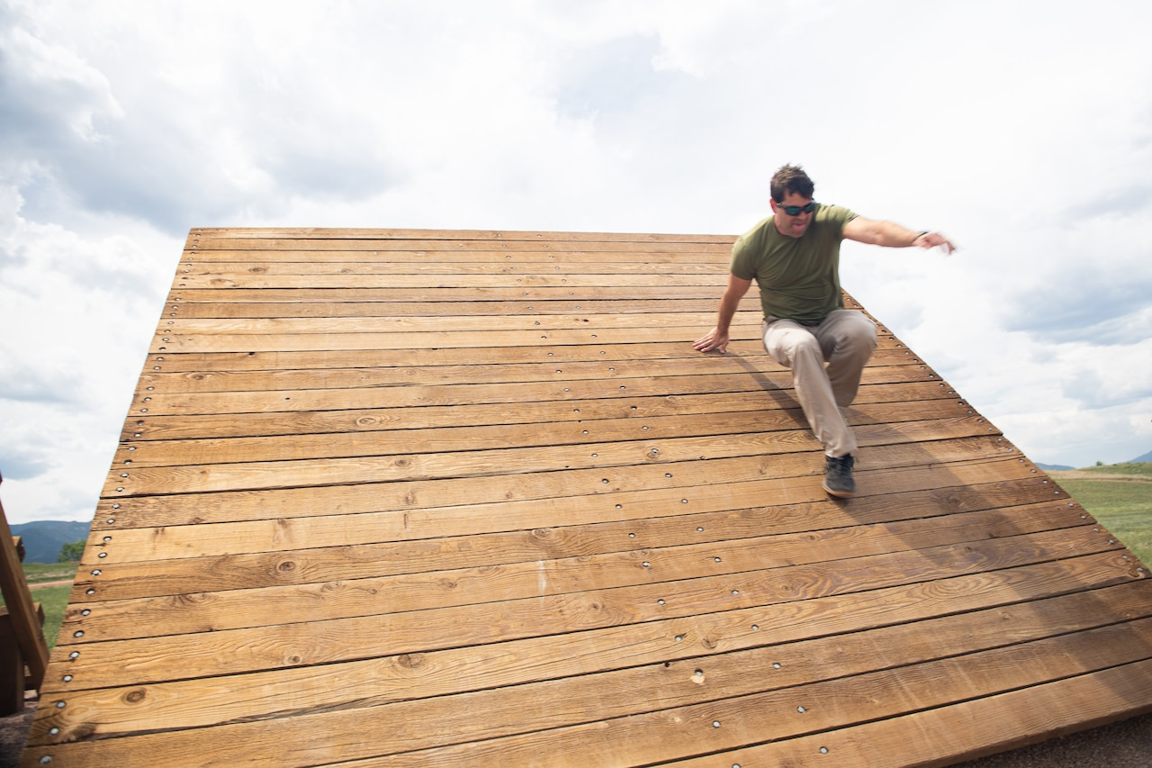 A civilian walks on a wood structure.