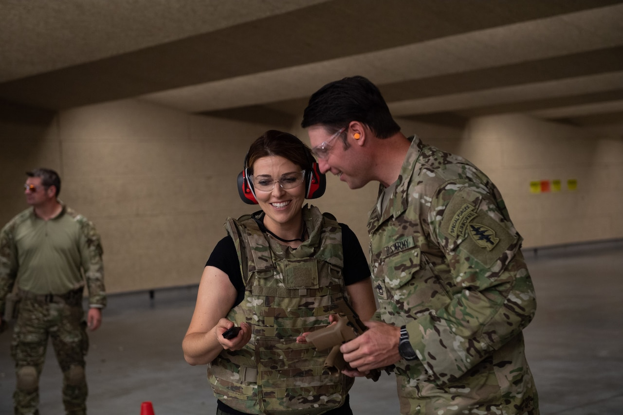 A soldier talks to a civilian wearing a protective vest and earphones.