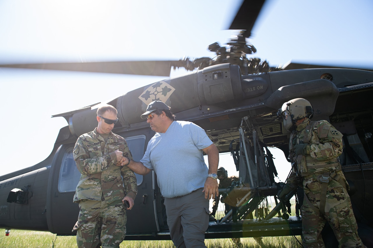 A civilian fist-bumps a soldier outside a helicopter.