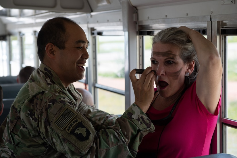 A soldier paints a civilian's face.