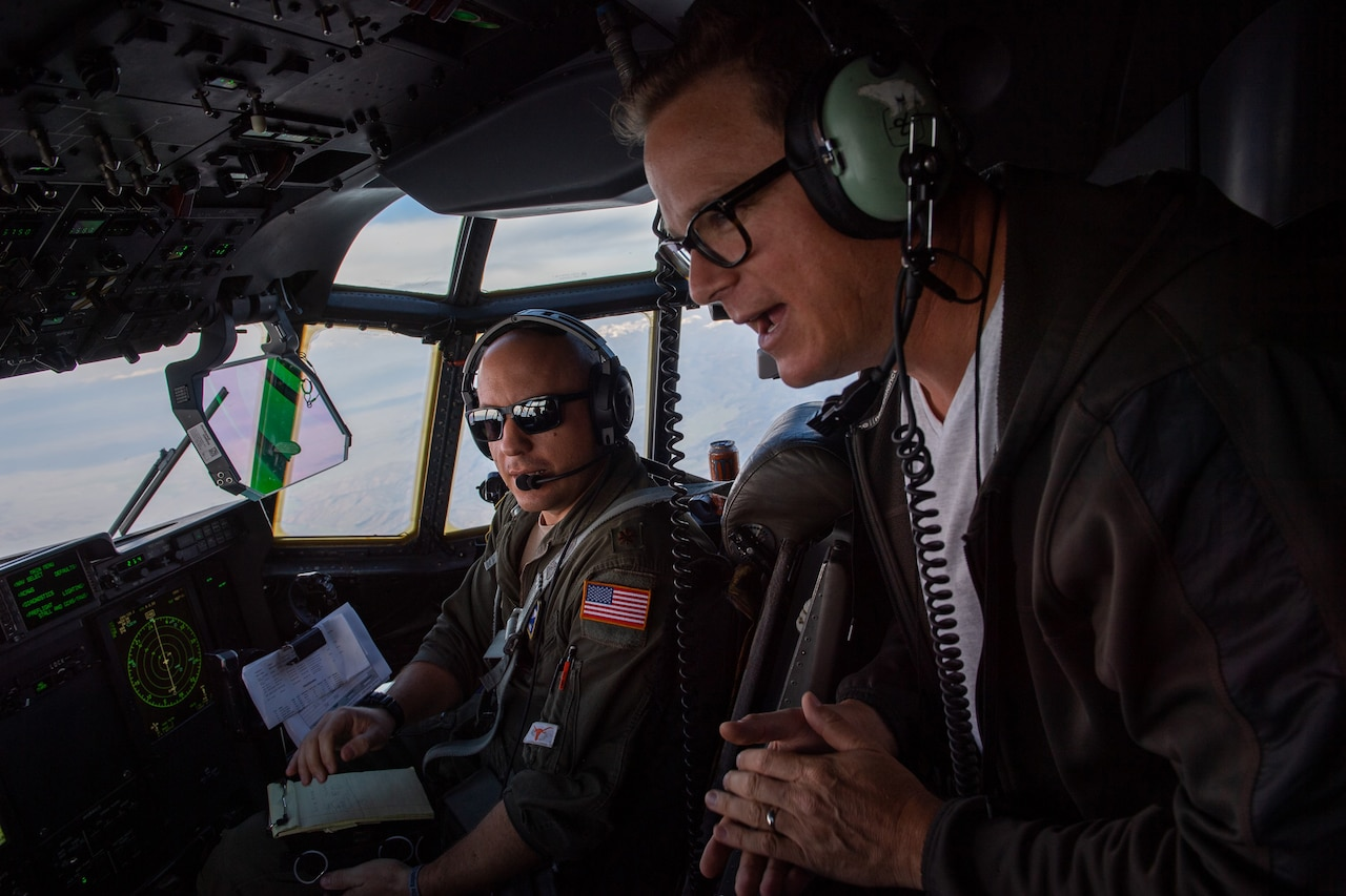 A civilian and as service member talk in an aircraft cockpit.