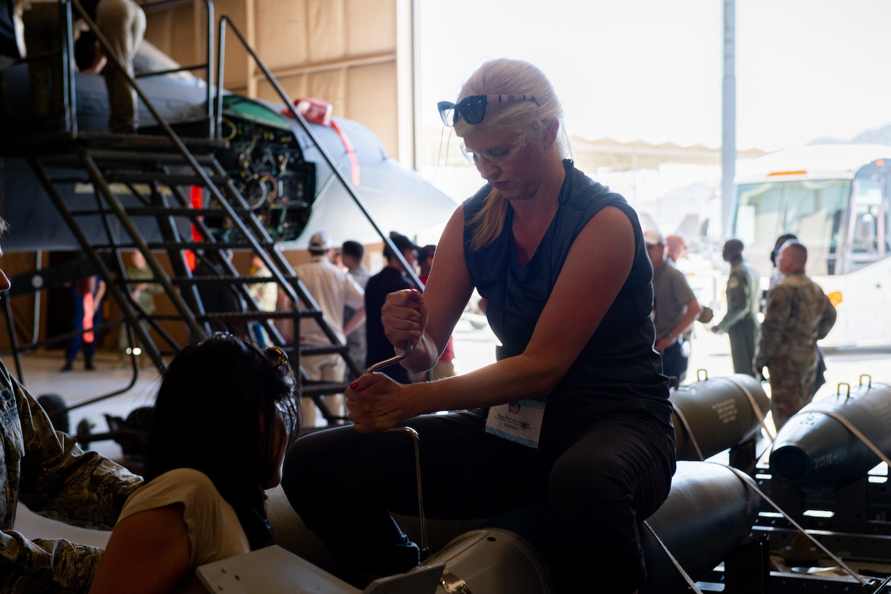 A civilian sits atop a projectile in a hangar-type space and works on it with a tool.