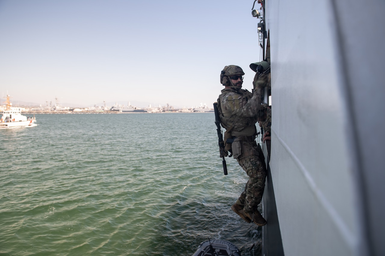 A service member climbs on the side of a ship in the water.