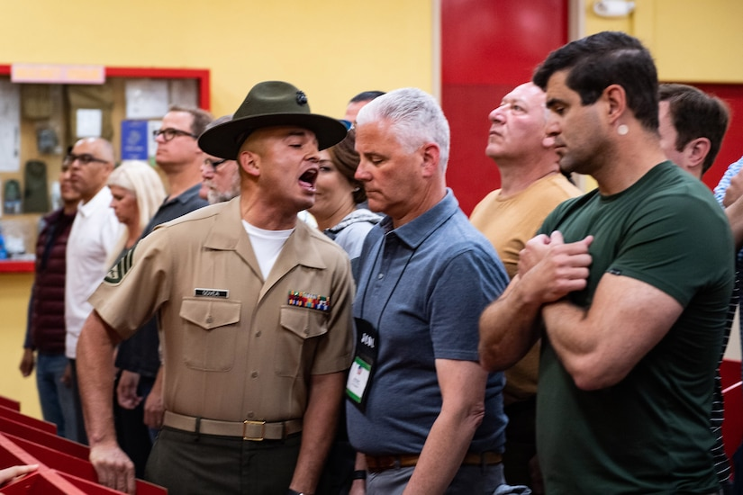 A Marine shouts and gets in the face of a civilian standing in a row of civilians.