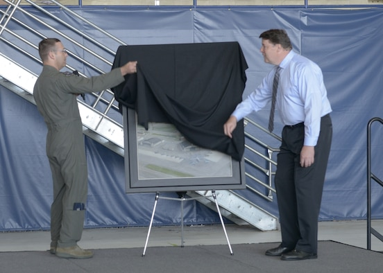 U.S. Air Force Col. Robert Davis, 3rd Wing commander, and John Hume, an artist, reveal a commemorative painting during the opening ceremony for the 3rd Wing's 100th anniversary celebration on Joint Base Elmendorf-Richardson, Alaska, July 25, 2019.