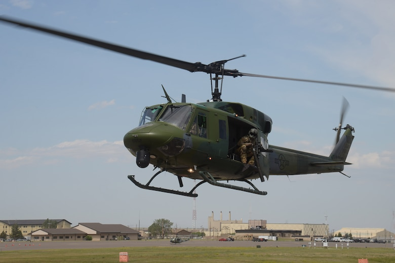 A UH-1N helicopter carrying tactical response force members chase a vehicle during a training event July 24, 2019, at Malmstrom Air Force Base, Mont.