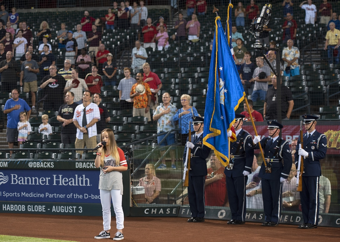 An Arizona Diamondbacks fan sings the national anthem in front of the Luke Air Force Base Honor Guard, July 24, 2019, at Chase Field in Phoenix.
