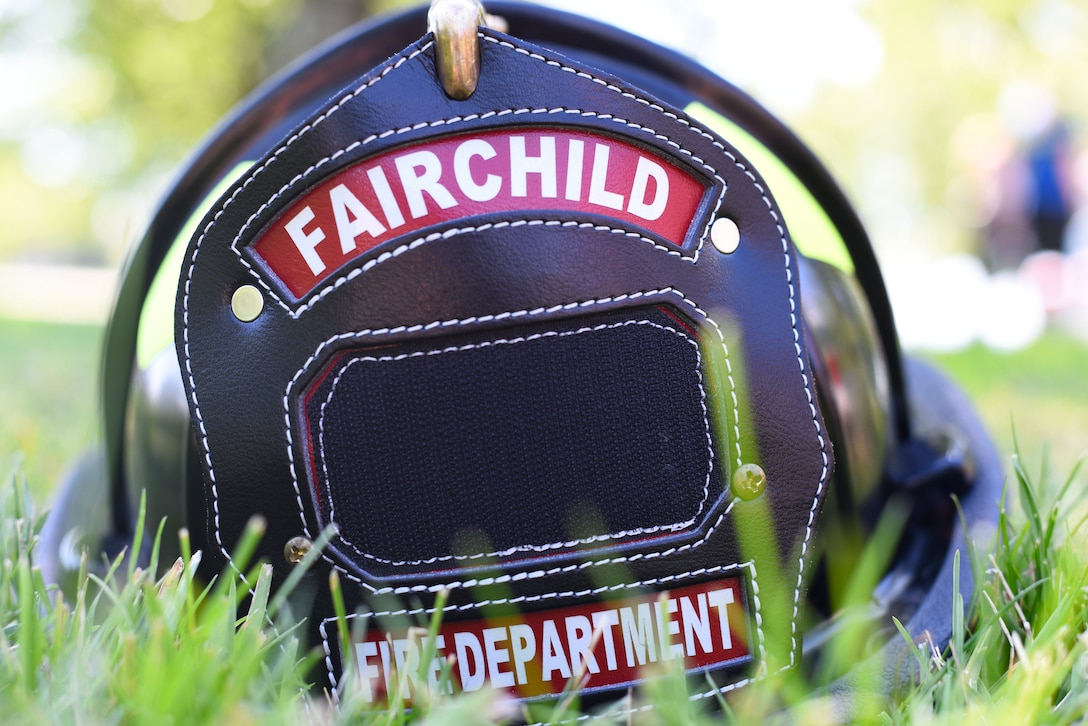 A firefighter's helmet from Fairchild's fire department rests in the grass during the Summer Youth Fair at Fairchild Air Force Base, Washington, July 25, 2019. Members from Fairchild's 92nd Civil Engineer Squadron Fire Department, Explosive Ordnance Disposal team, 92nd Security Forces Squadron and 92nd Medical Group provided activities and educational exhibits. (U.S. Air Force photo by Airman 1st Class Lawrence Sena)