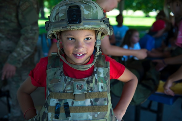 A child from Fairchild's Youth Center tries on protective gear from the 92nd Civil Engineer Squadron Explosive Ordnance Disposal flight during the Summer Youth Fair at Fairchild Air Force, Washington, July 25, 2019. Approximately 100 children from across Fairchild participated in the fair. (U.S. Air Force photo by Airman 1st Class Lawrence Sena)