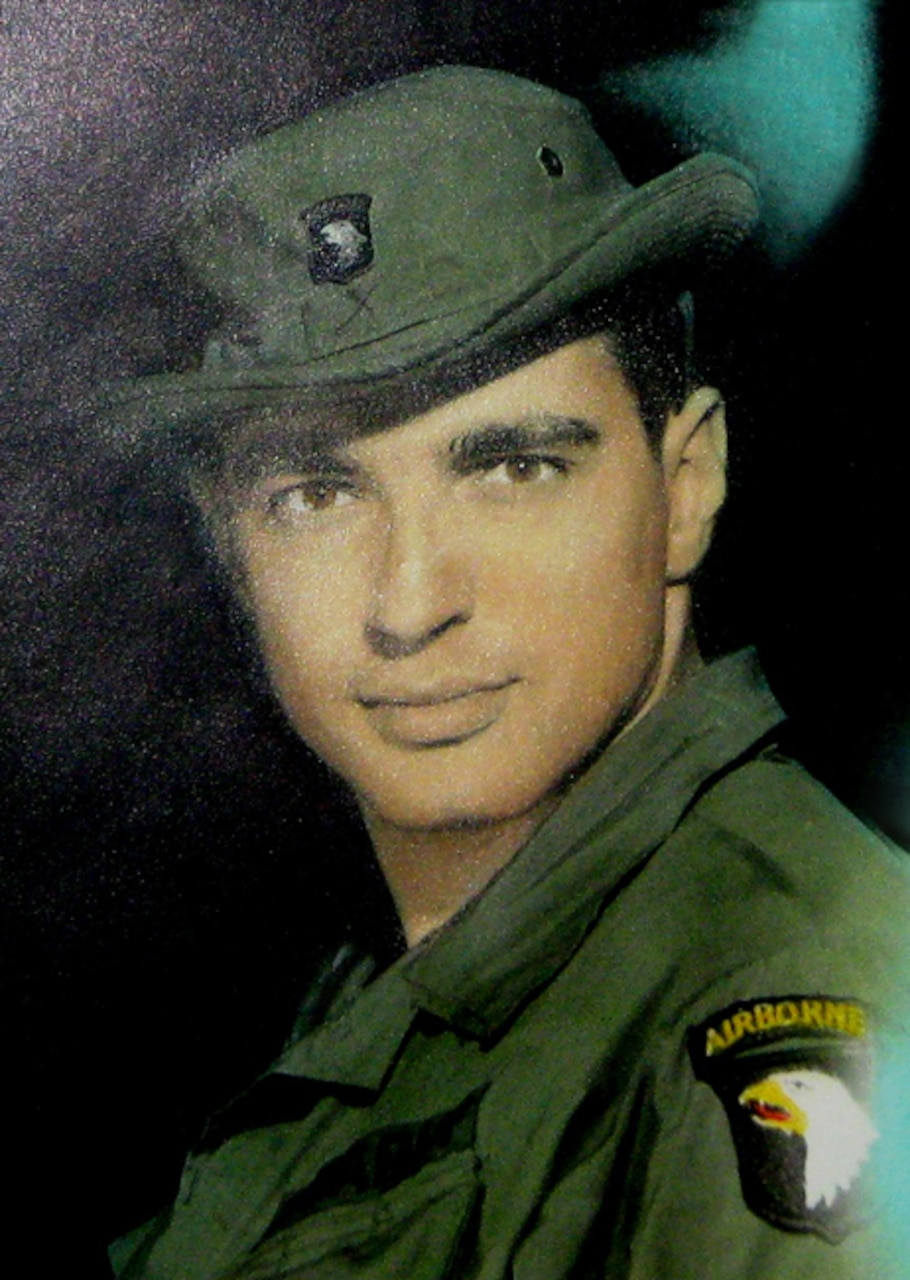 A man wearing a green military uniform with a 101st Airborne Division patch and matching bucket hat looks into the camera.