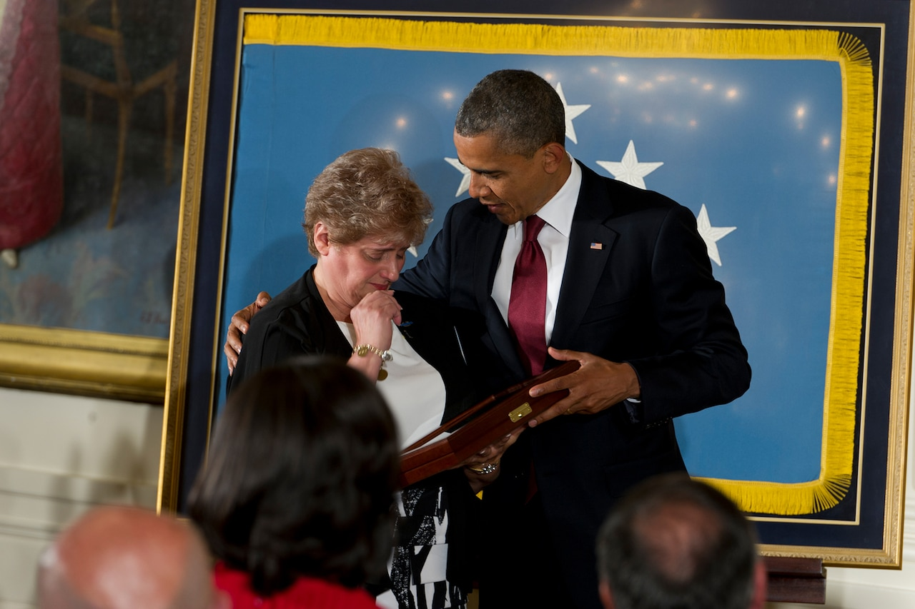 President Barack Obama has his hand around the shoulder of a woman who is holding and looking at a case with a Medal of Honor in it.