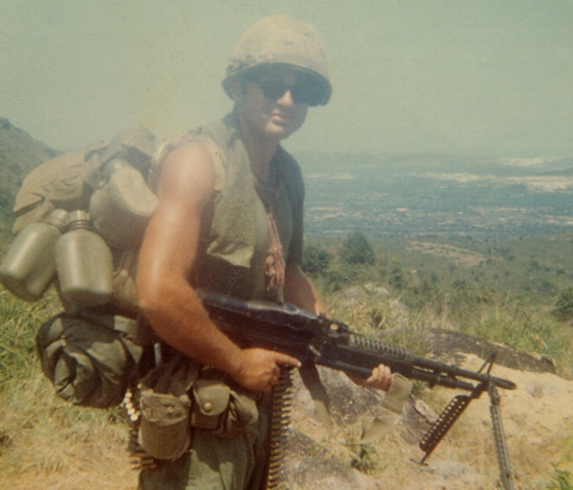 A sleeveless soldier wearing a helmet and carrying a backpack, lots of ammunition and several water bottles poses on a mountainside for a photo with his rifle.