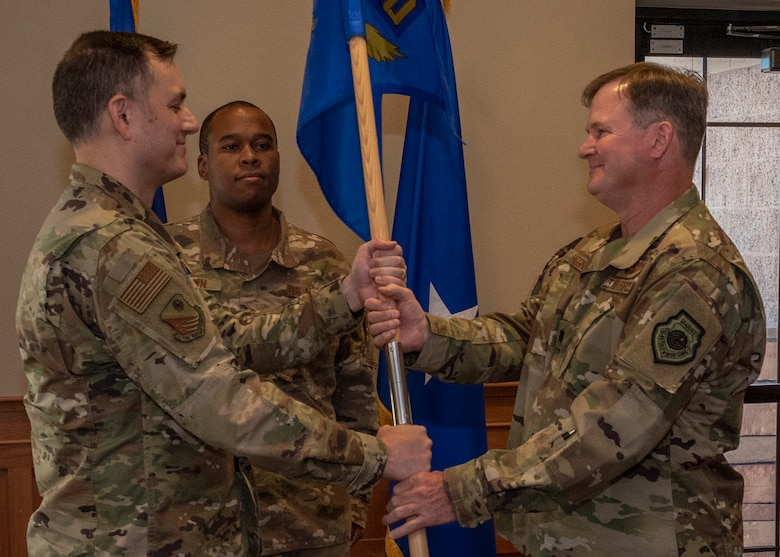 Brig. Gen. David W. Snoddy, U.S Air Force Warfare Center vice commander, passes the Air Force Joint Test Program Office's guidon to incoming commander Lt. Col. Sean M. Higgins at a change of command ceremony at Nellis Air Force Base, Nev., June 28, 2019. The Joint Test & Evaluation program is designed to help solve inter-service operational problems in a joint environment and alleviate test and evalution difficulties through work on testing methodologies. (U.S. Air Force photo by Airman 1st Class Dwane R. Young)