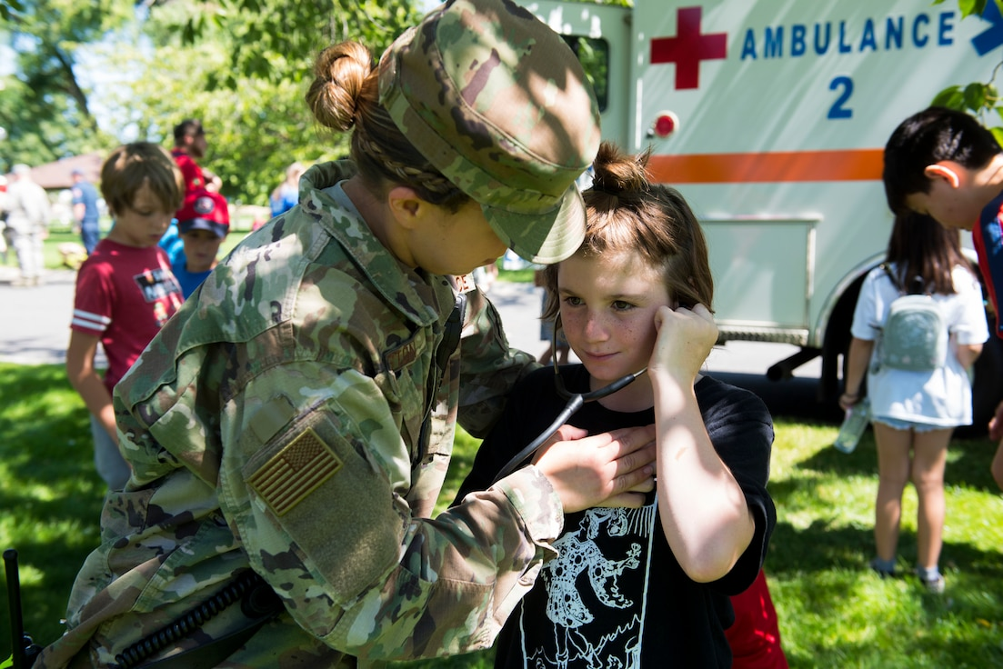 U.S. Air Force Staff Sgt. Sara Huston, 92nd Health Care Operations Squadron medical technician, shows a kid how to use a stethoscope during the Summer Youth Fair at Fairchild Air Force Base, Washington, July 25, 2019. Approximately 100 children from across Fairchild participated in the fair. (U.S. Air Force photo by Airman 1st Class Lawrence Sena)