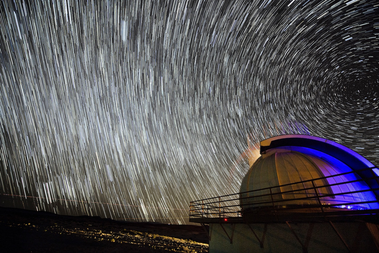 Stars illuminate the sky over a domed structure.