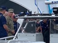 Military personnel board a boat.
