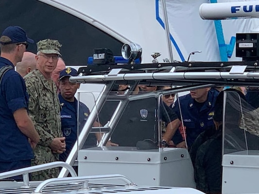 Military personnel board a boat.