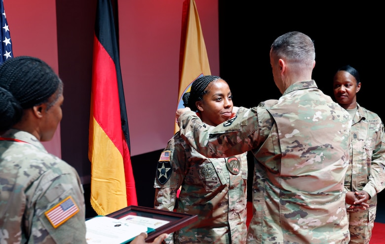 Command Sgt. Maj. Rocky L. Carr, 21st Theater Sustainment Command senior enlisted advisor, presents the Sergeant Morales Club medallion to Sergeant 1st Class Natasha Carroll, cargo specialist, 1st Inland Cargo Transfer Company, 16th Sustainment Brigade, 21st Theater Sustainment Command during the Sergeant Morales Club induction ceremony, July 10 at the Kleber Kaserne Theater in Kaiserslautern, Germany.