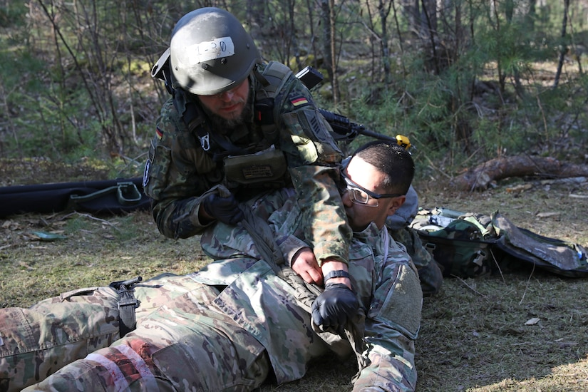 Bundeswehr OF4 Olivier Keller performs medical aid on a simulated casualty as part one of the various medical lanes candidates will have to go through in order to obtain the Expert Field Medical Badge (EFMB) at Grafenwoehr Training Area, Germany, March 29, 2019. For qualification for the EFMB badge, Soldiers must endure a multitude of events such as land navigation, physical fitness test, medical evacuations, weapons function checks, ruck march, chemical biological radioactive nuclear evaluations, written test, and medical treatments. (U.S. Army photo by Spc. Elliott Page)