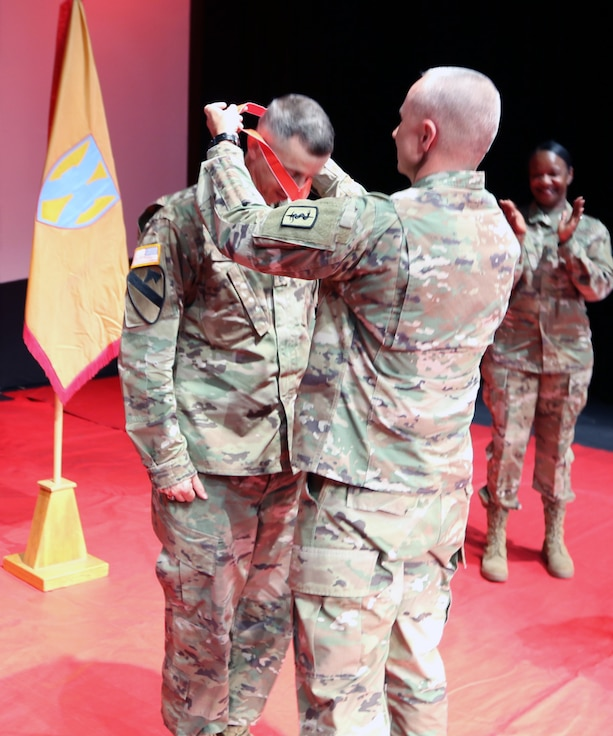 Command Sgt. Maj. Matthew P. Baller, 30th Medical Brigade, 21st Theater Sustainment Command senior enlisted advisor, presents the Sergeant Morales Club medallion to Command Sgt. Maj. Rocky L. Carr, 21st Theater Sustainment Command senior enlisted advisor, during the Sergeant Morales Club induction ceremony, July 10 at the Kleber Kaserne Theater in Kaiserslautern, Germany. Carr was inducted as an honorary member of the program, after having been previously inducted into the Sergeant Audie Murphy Club.