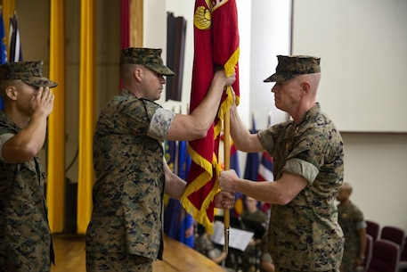 U.S. Marine Corps Sgt. Maj. Michael J. West presents the Marine Corps to U.S. Marine Corp Maj. Gen. Paul J. Rock Jr. during the 3D Marine Expeditionary Brigade assumption of command at the Camp Courtney Theater, July 26, 2019. Rock assumes command as the deputy commanding general of the III Marine Expeditionary Force and commanding general of the 3rd Marine Expeditionary Brigade. The assumption of command ceremony represents the relinquishing of power from one commanding general to another. (U.S. Marine Corps photo by Sgt. George Melendez)