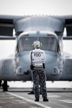 The Fllight Deck Officer watches on as a United States Marines MV-22B Osprey conducts landings on HMAS Canberra during Exercise Talisman Sabre 2019. Talisman Sabre 2019 is a bilateral combined Australian and United States training activity.    TS19 is designed to practice our respective military services and associated agencies in planning and conducting Combined and Joint Task Force operations, and improve the combat readiness and interoperability between Australian and US forces.    TS19 will be the eighth iteration of the exercise and consists of a Field Training Exercise incorporating force preparation (logistic) activities, amphibious landings, land force manoeuvre, urban operations, air operations, maritime operations and Special Forces activities.    (Photo by Richard Cardell)