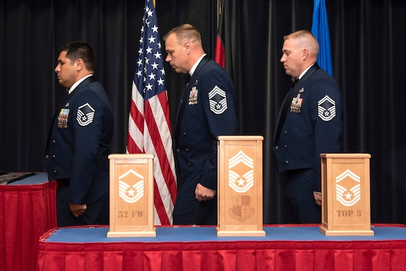 U.S. Air Force Master Sgt. Samuel Jalomo, 52nd Security Forces Squadron operations NCO in charge, left, Chief Master Sgt. James Andrews, 52nd Aircraft Maintenance Squadron superintendent, center, and Senior Master Sgt. Aaron Townsend, 52nd Maintenance Squadron lead production superintendent, conduct a candle lighting ceremony during a senior NCO induction ceremony at Spangdahlem Air Base, Germany, July 26, 2019. The three candle pillars symbolize progression through the top tier of the enlisted ranks. (U.S. Air Force photo by Airman 1st Class Valerie Seelye)
