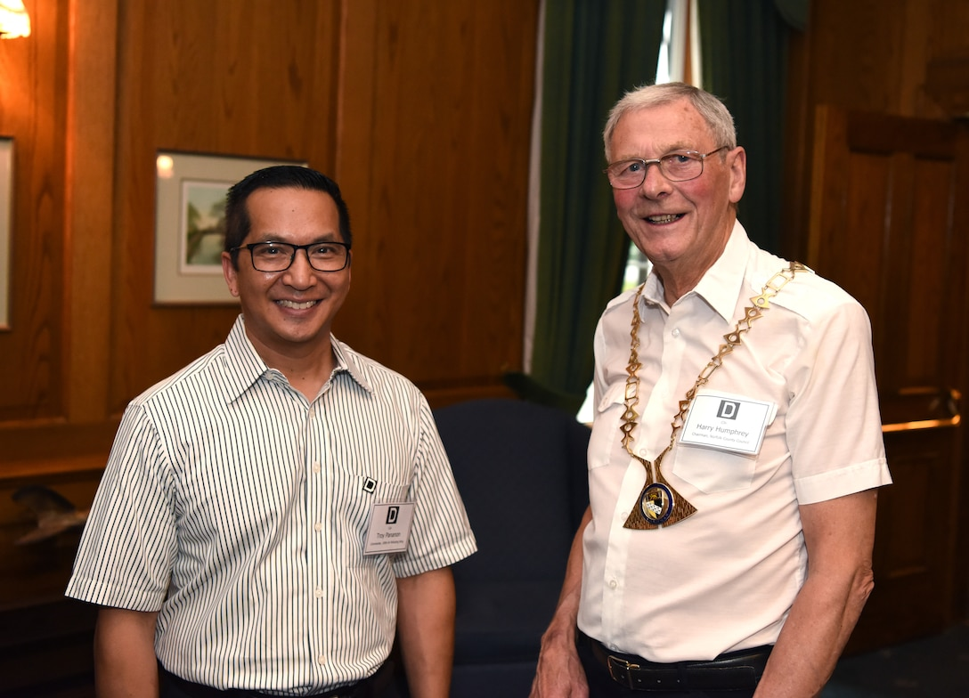 U.S. Air Force Col. Troy Pananon, 100th Air Refueling Wing commander, and Councillor Harry Humphrey, Norfolk County Council chairman, pose for a photo during the New Mayors' Barbecue at RAF Mildenhall, England, July 27, 2019. During the event, Pananon covered a number of topics, ranging from the economic effect Airmen have on the community to the history of the base. The event provided a casual setting where local community leaders could build partnerships with base leadership. (U.S. Air Force photo by Airman 1st Class Brandon Esau)