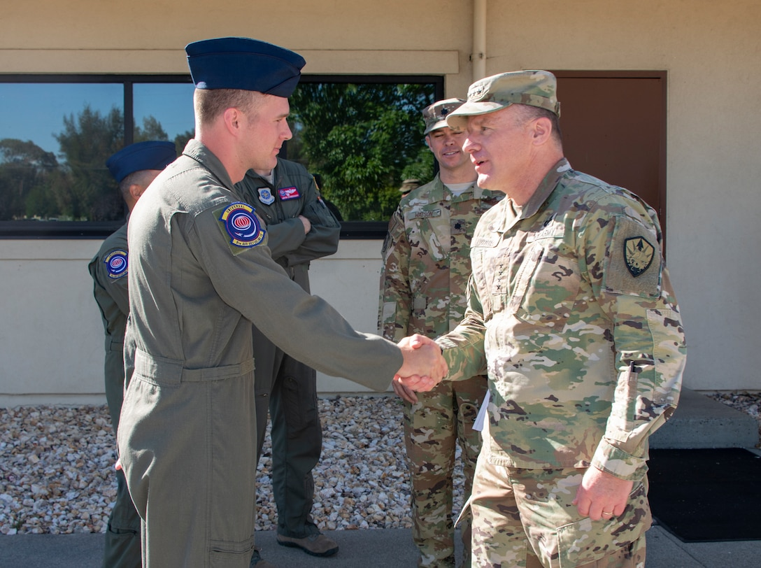 U.S. Army Gen. Steve Lyons, right, U.S. Transportation Command commander, Scott Air Force Base, Illinois, recognizes Airman 1st Class Taran Lewis, 9th Air Refueling Squadron in-flight refueling specialist, for superior performance, July 24, 2019 at Travis Air Force Base, California. Lyons interacted with Travis Airmen and toured several units while on the base visit. (U.S. Air Force photo by Heide Couch)