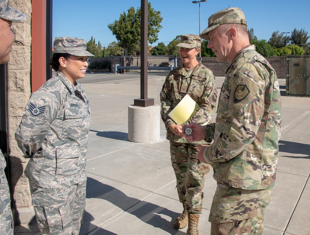 U.S. Army Gen. Steve Lyons, right, U.S. Transportation Command commander, Scott Air Force Base, Illinois, recognizes Staff Sgt. Cherielyn Amaba, 60th Diagnostics and Therapeutics Squadron noncommissioned officer in charge of mammography, as a star performer, July 24, 2019 at Travis Air Force Base, California. Lyons had the opportunity to interact with Travis Airmen and tour several units while on the base visit. (U.S. Air Force photo by Heide Couch)