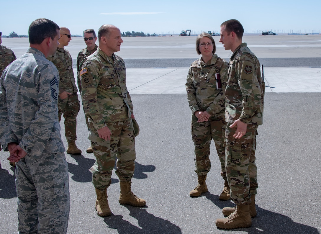 U.S. Army Gen. Steve Lyons, center, U.S. Transportation Command commander, Scott Air Force Base, Illinois, listens to Lt. Col. Kelly Smith, 60th Aerial Port Squadron commander, and Capt. Joshua Cross, 60th APS operations officer, right, July 24, 2019 at Travis Air Force Base, California. Lyons had the opportunity to interact with Travis Airmen and tour several units while on the base visit. (U.S. Air Force photo by Heide Couch)