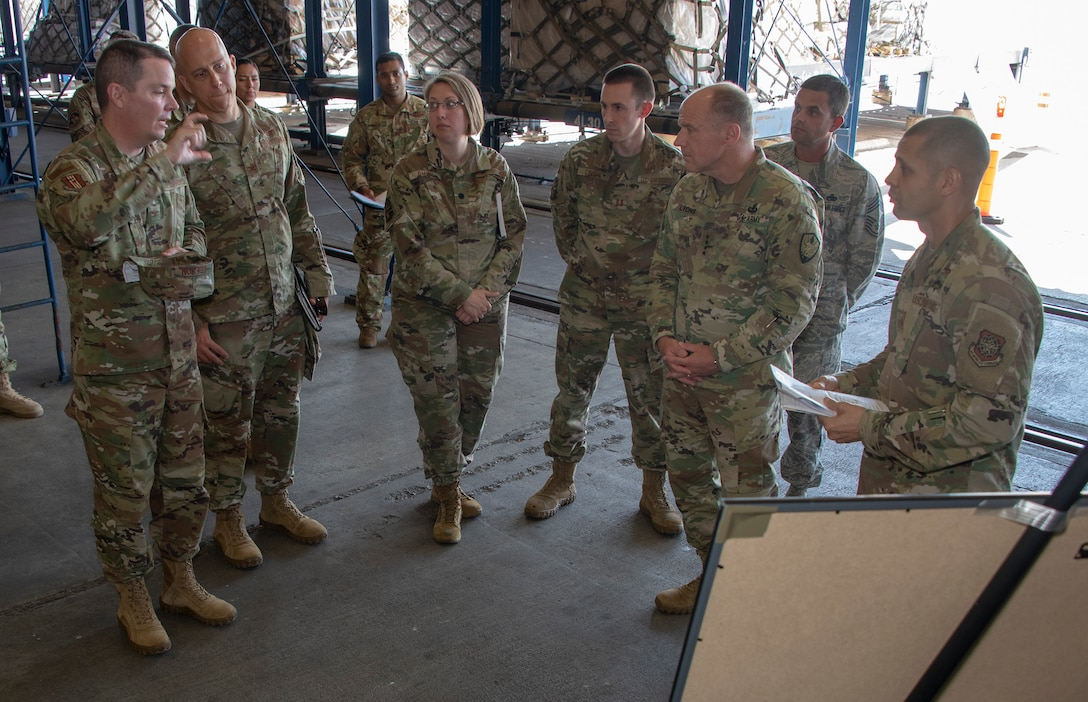 U.S. Army Gen. Steve Lyons, center left, U.S. Transportation Command commander, Scott Air Force Base, Illinois, listens to Col. Jeffrey Nelson, far left, 60th Air Mobility Wing commander, during a visit to the 60th Aerial Port Squadron warehouse, July 24, 2019 at Travis Air Force Base, California. Lyons had the opportunity to interact with Travis Airmen and tour several units while on the base visit. (U.S. Air Force photo by Heide Couch)