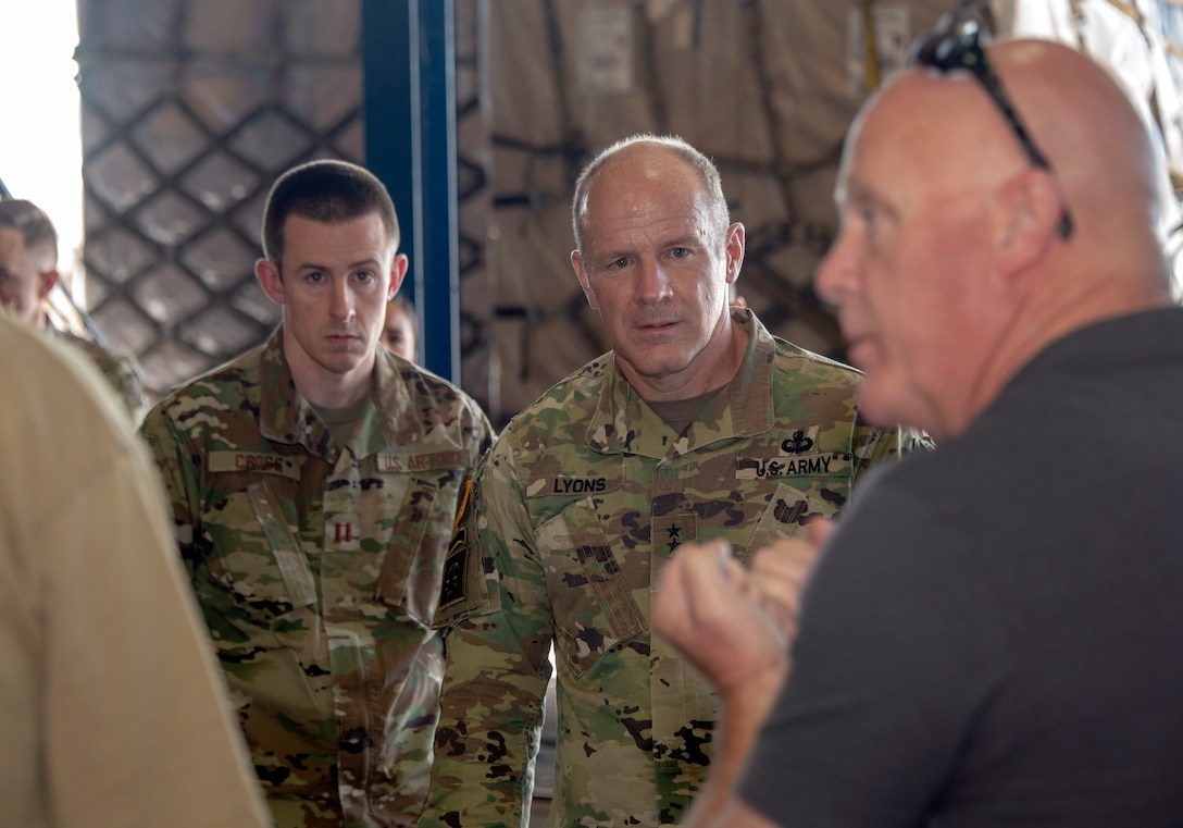 U.S. Army Gen.l Steve Lyons, center, U.S. Transportation Command commander, Scott Air Force Base, Illinois, listens to John Buchanan, right, 60th Aerial Port Squadron transportation operations officer, during a visit to the 60th APS warehouse, July 24, 2019 at Travis Air Force Base, California. Lyons had the opportunity to interact with Travis Airmen and tour several units while on the base visit. (U.S. Air Force photo by Heide Couch)